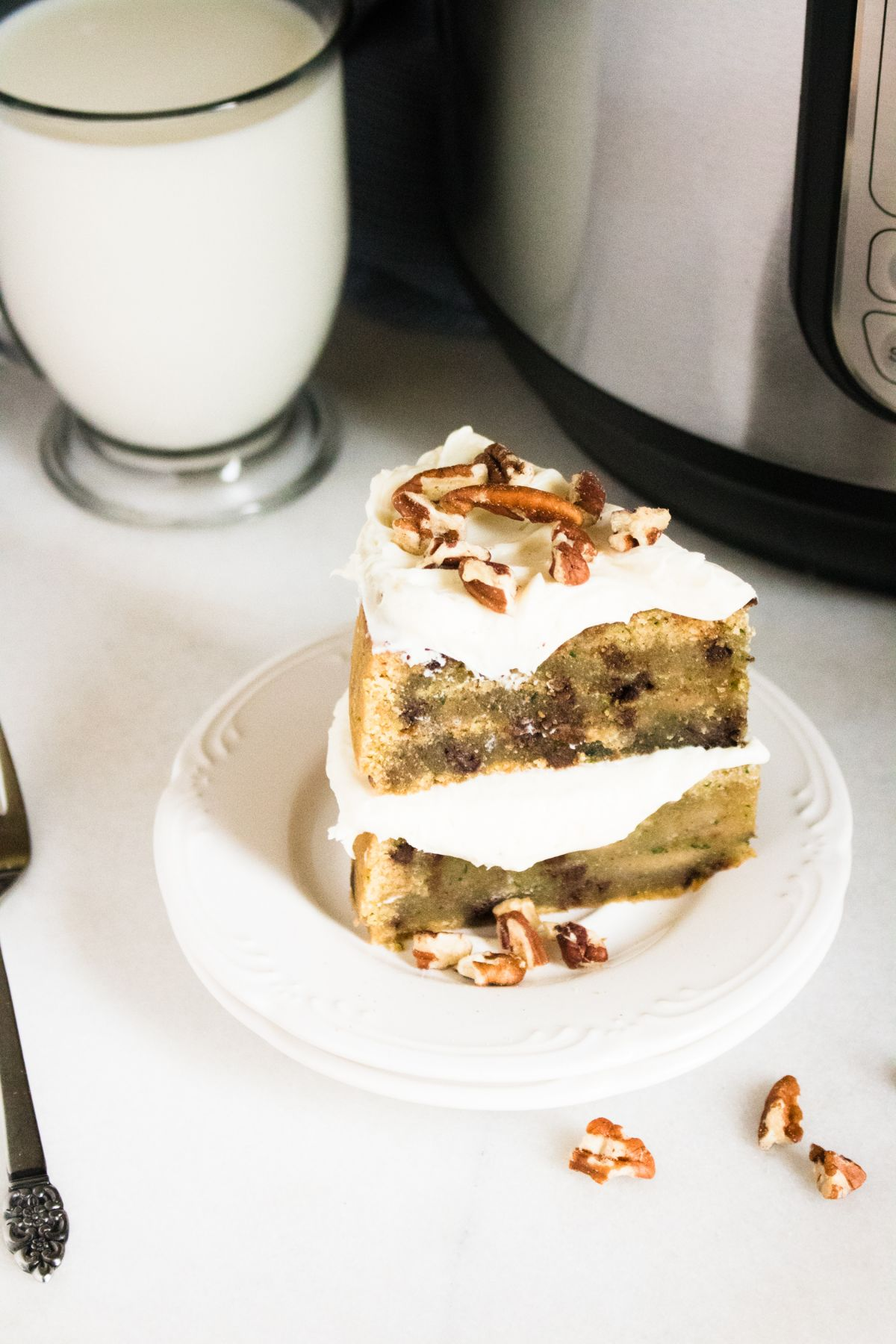 A zoomed in image of a slice of Zucchini bread with on a serving plate with a glass of milk in background