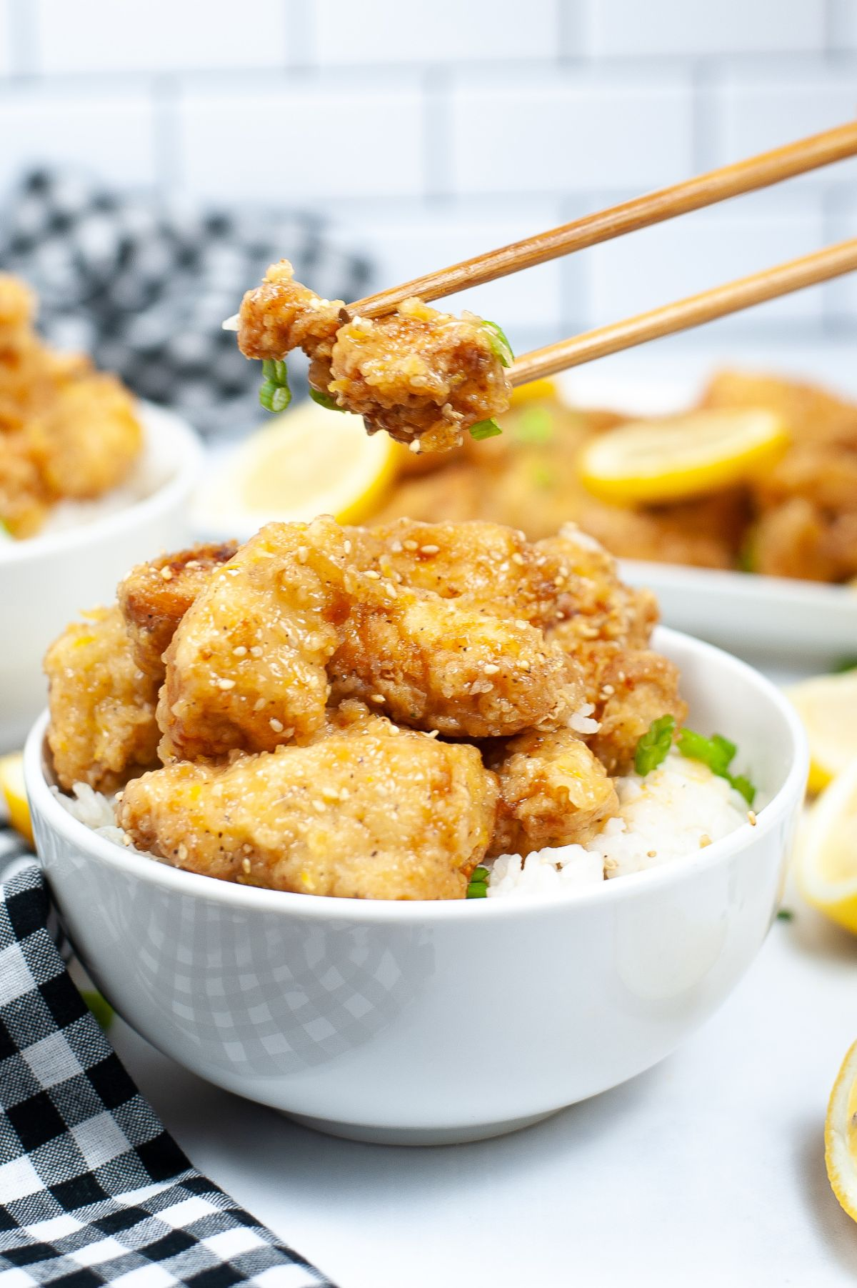 chopsticks holding a piece of chicken above a bowl of lemon chicken and rice
