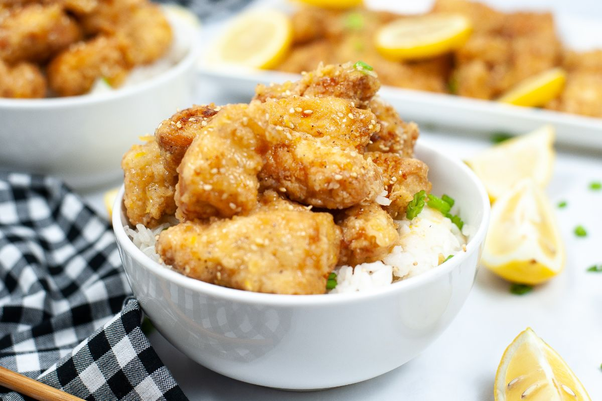 Chinese chicken dish in white bowl with lemon garnish and plate of chicken in background
