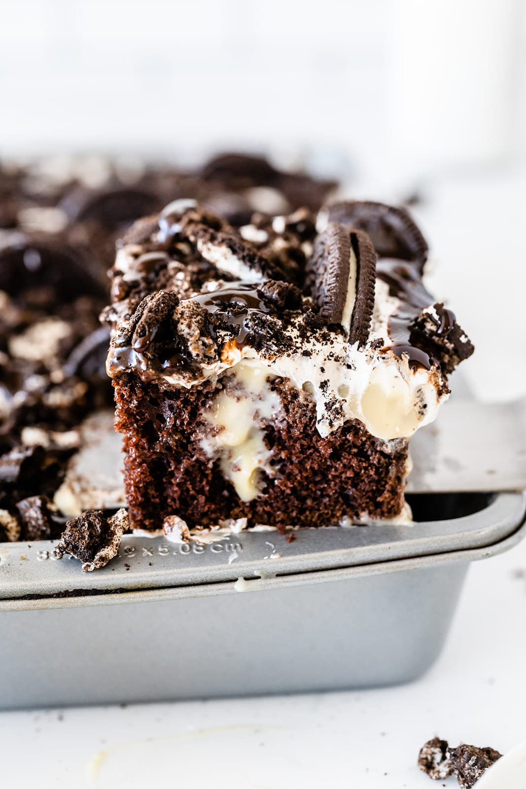 close up of a piece of Oreo poke cake with more cake in a pan in the background