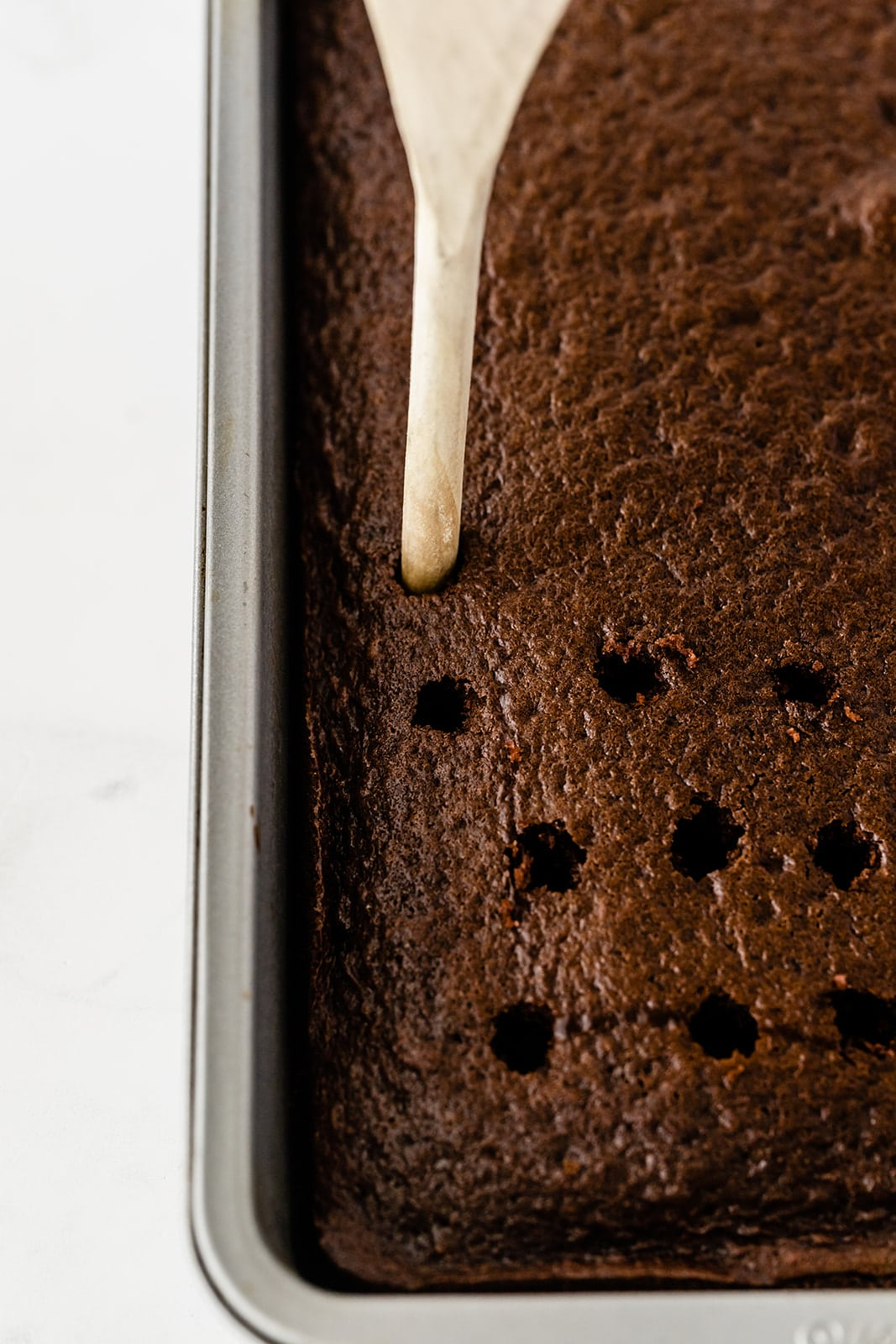 a wooden handle of a spoon being used to poke holes in a chocolate cake
