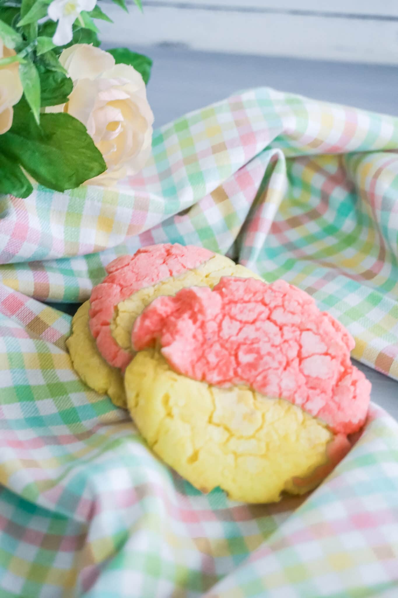 Strawberry Lemonade Crinkle Cookies on pastel colored plaid fabric next to a rose