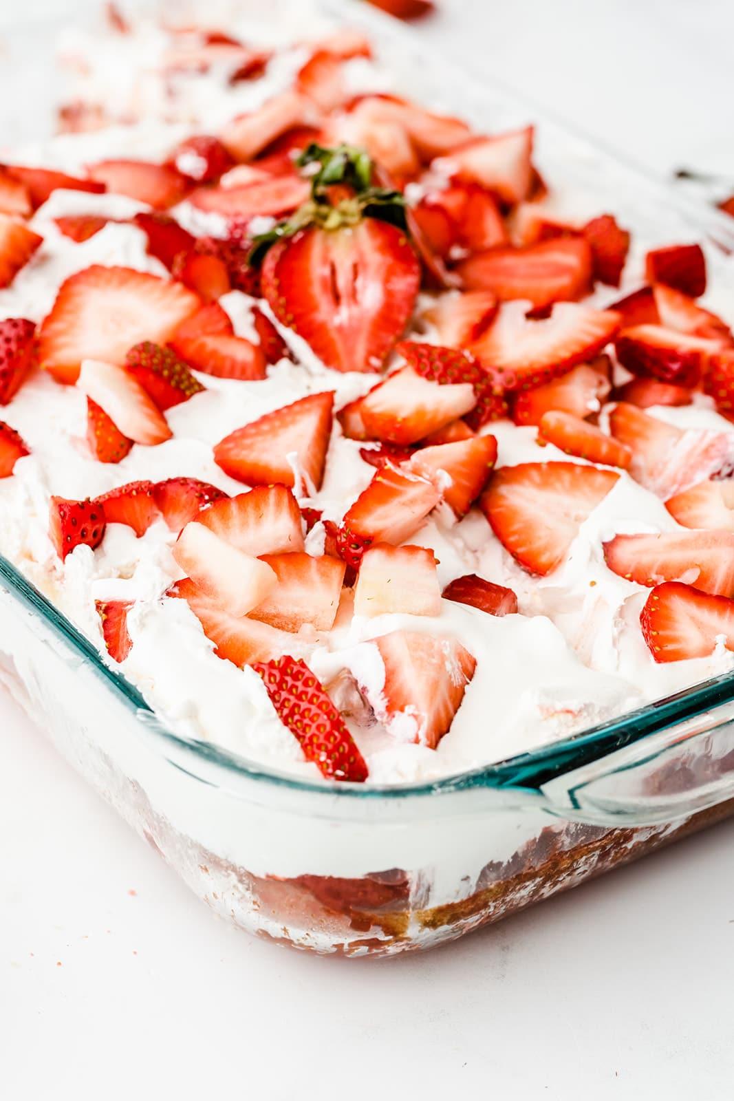 close up of a cake pan full of strawberry poke cake