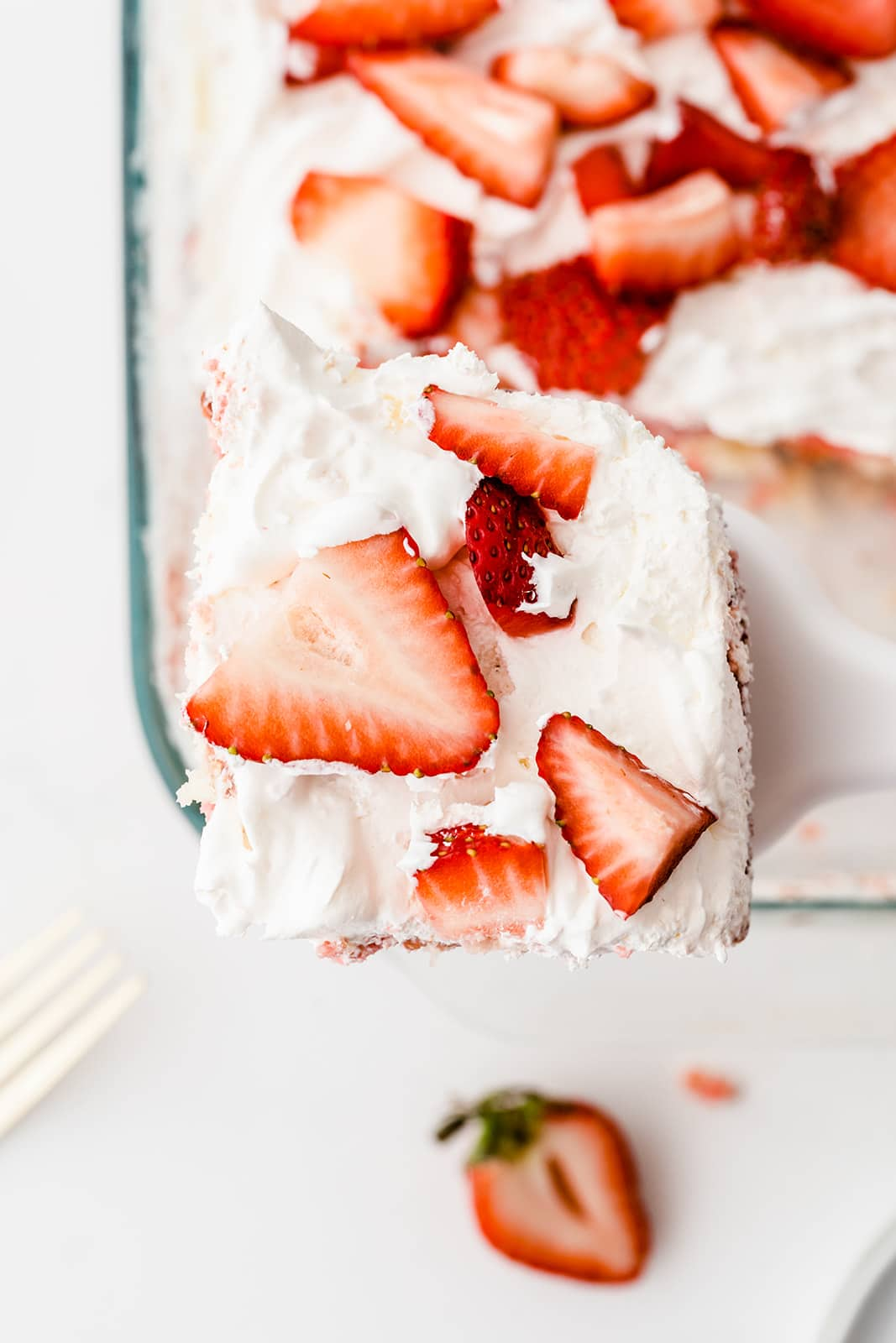 close up of a piece of strawberry poke cake