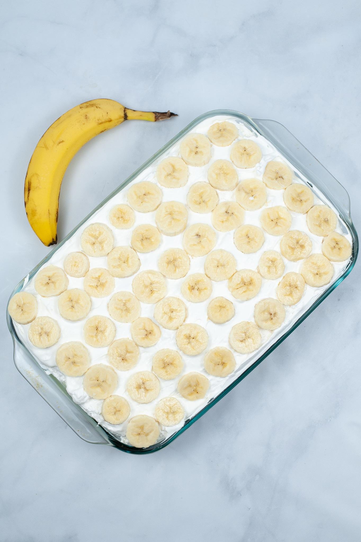 banana poke cake topped with bananas next to a banana