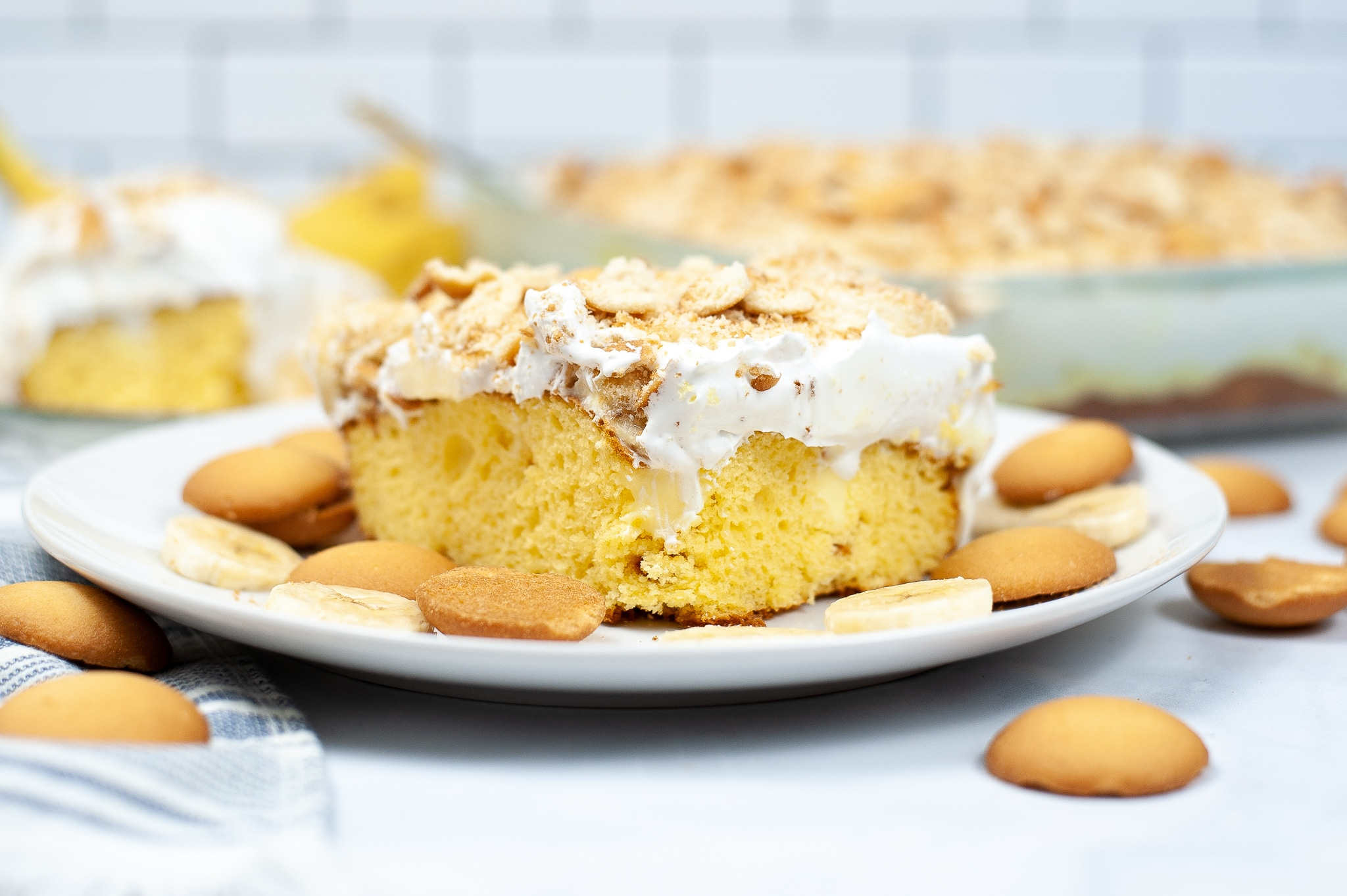 a closeup of a slice of Banana Pudding Poke Cake, vanilla wafers, and banana slices on a white plate