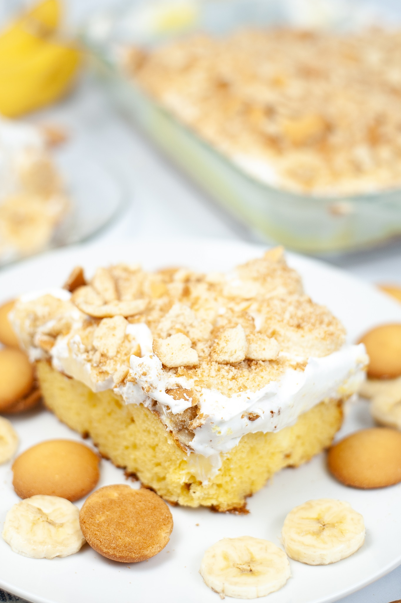 banana poke cake recipe on white plate surrounded by vanilla wafers and sliced bananas