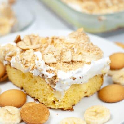 banana poke cake recipe on on white plate surrounded by vanilla wafers white plate surrounded by vanilla wafers and sliced bananas