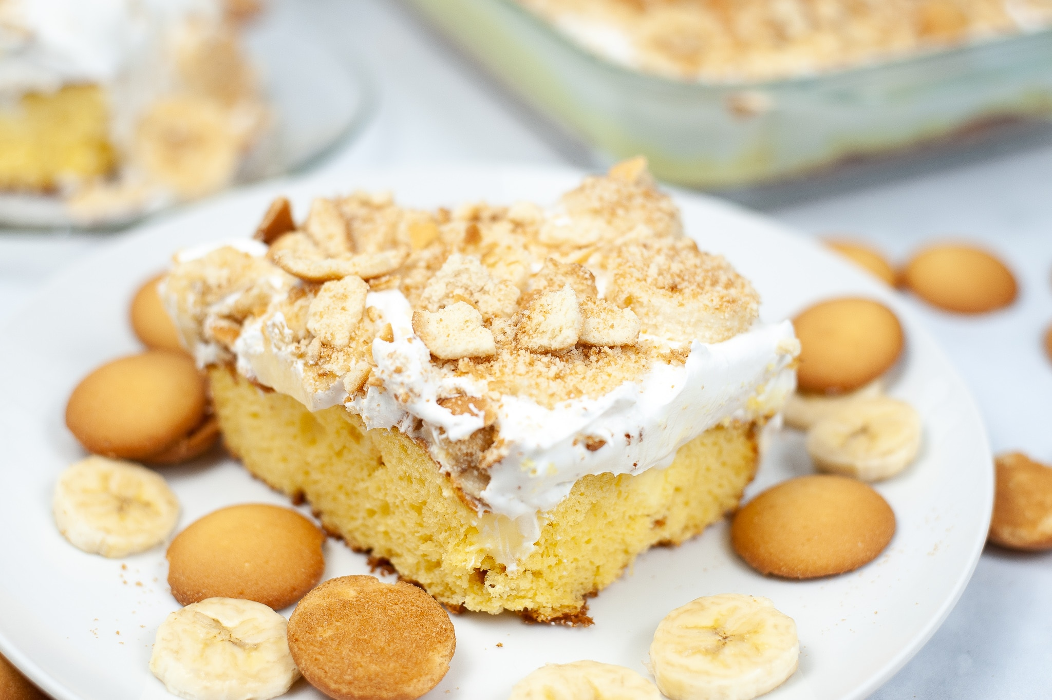 a close up of a slice of Banana Pudding Poke Cake, vanilla wafers, and banana slices on a white plate