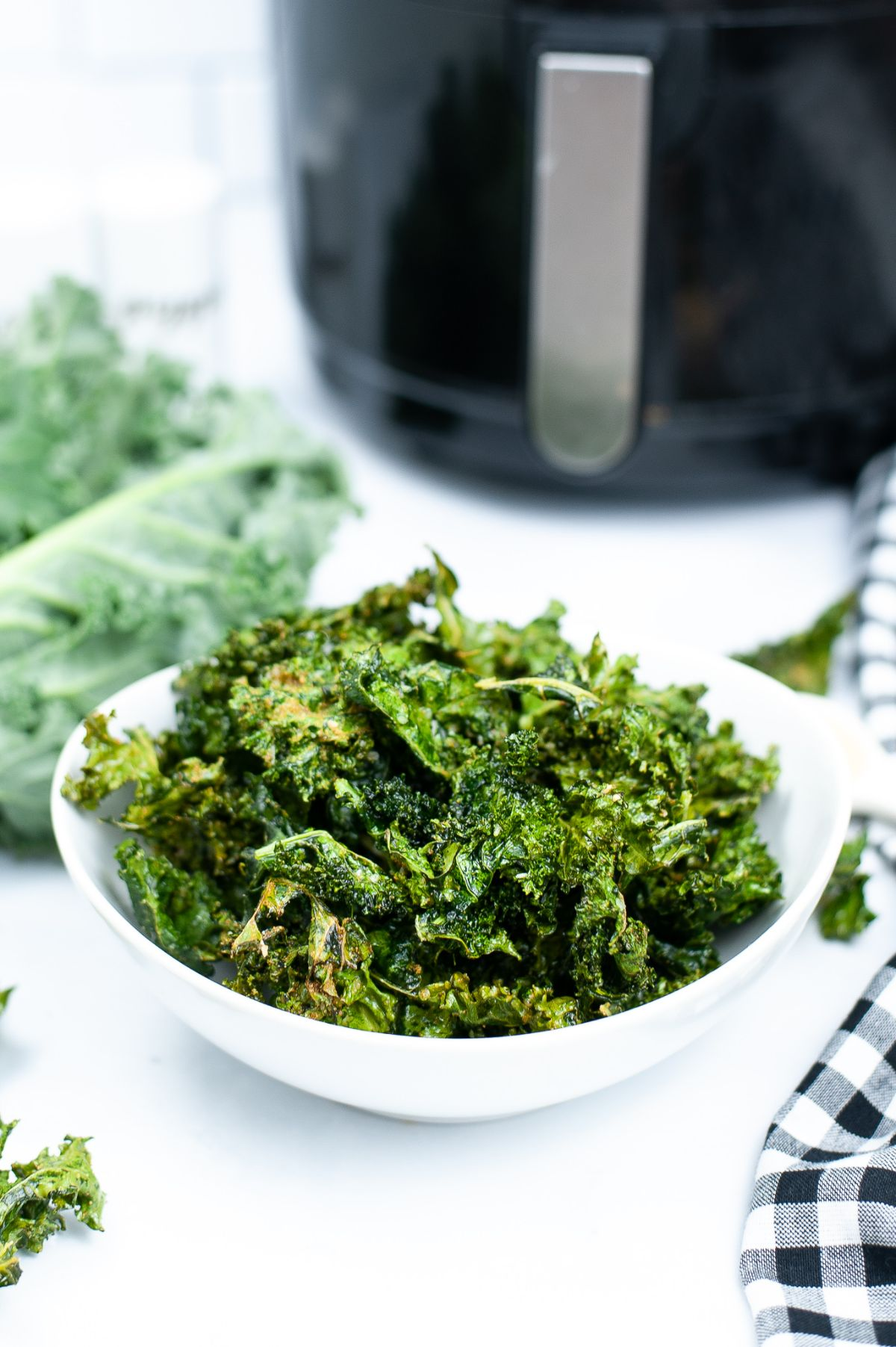 A vertical image of Air Fryer Kale Chips in a white bowl with a blurred air fryer in the background.