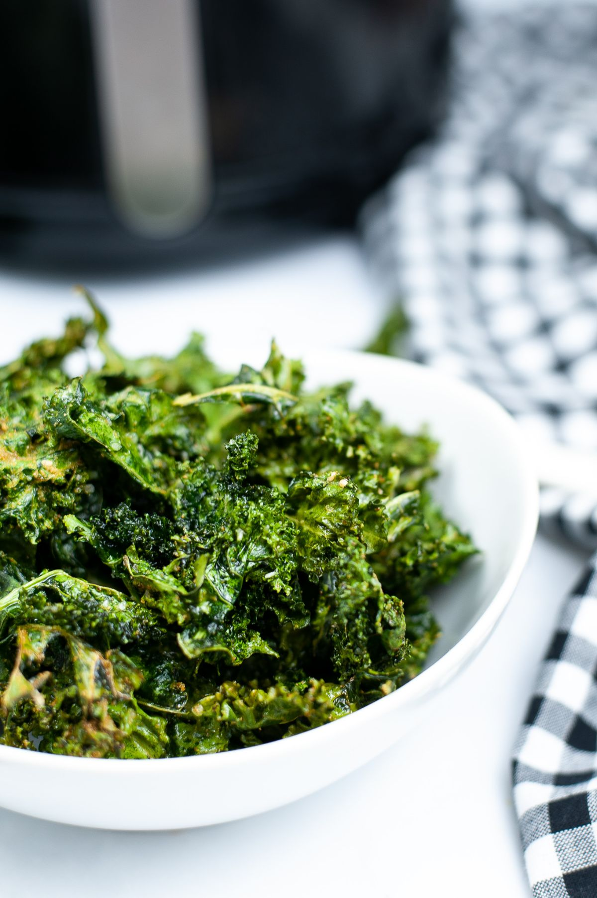 A vertical close up shot of the Air Fryer Kale chips highlighting the crispy Kale leaves.