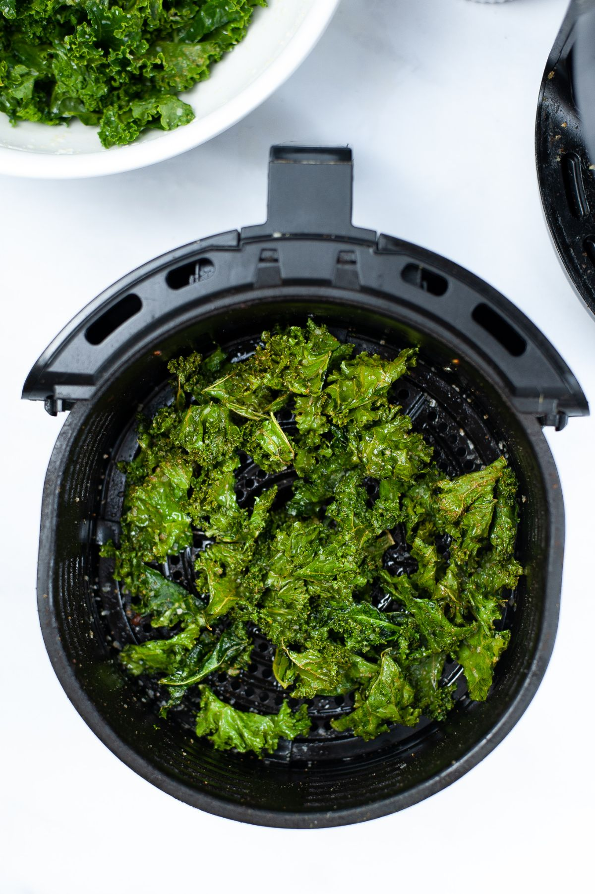 Kale chips in an air fryer basket just right after cooking.