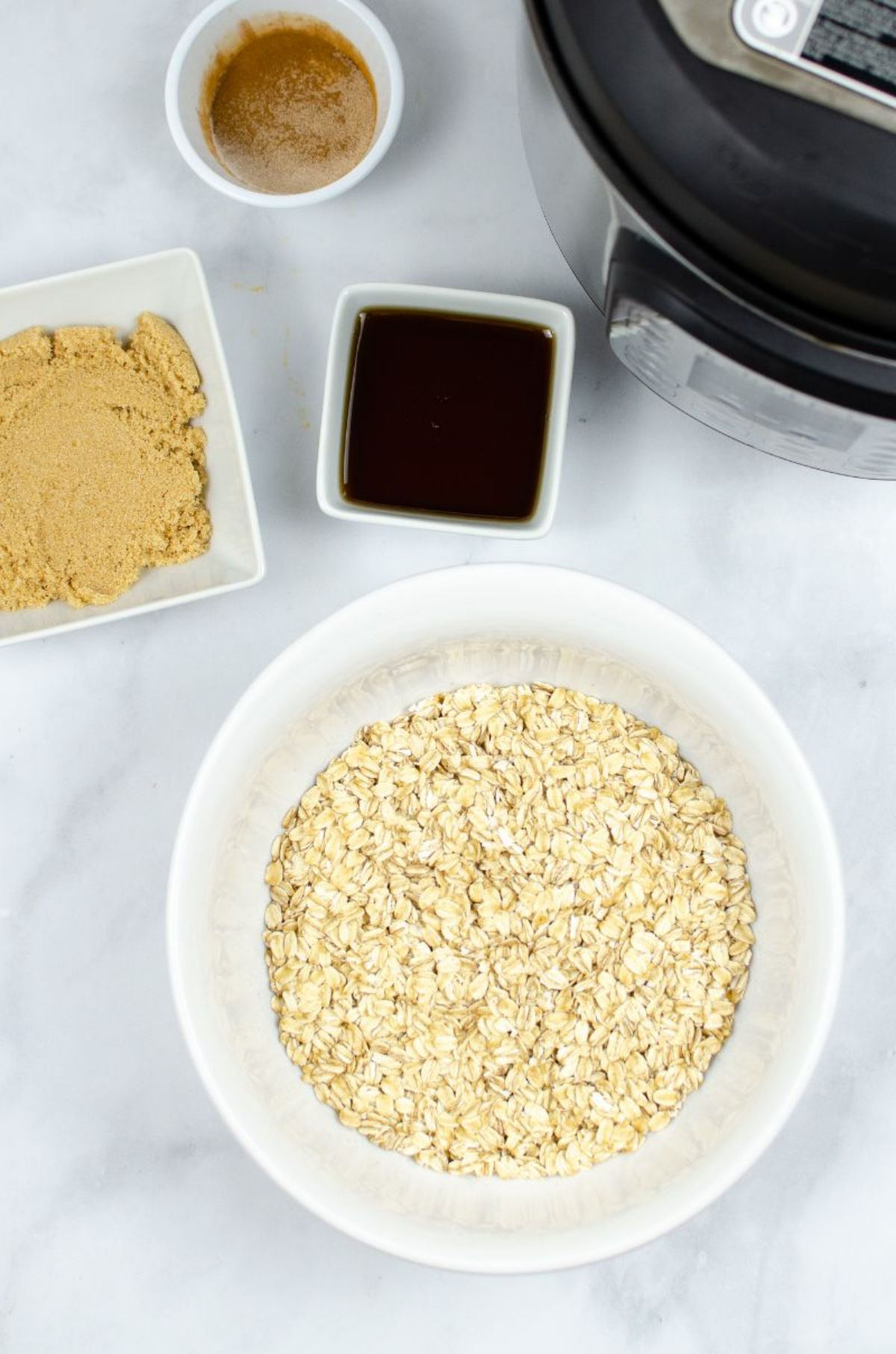 Ingredients used to make Instant Pot Oatmeal: oats, light brown sugar, maple syrup, and cinnamon.