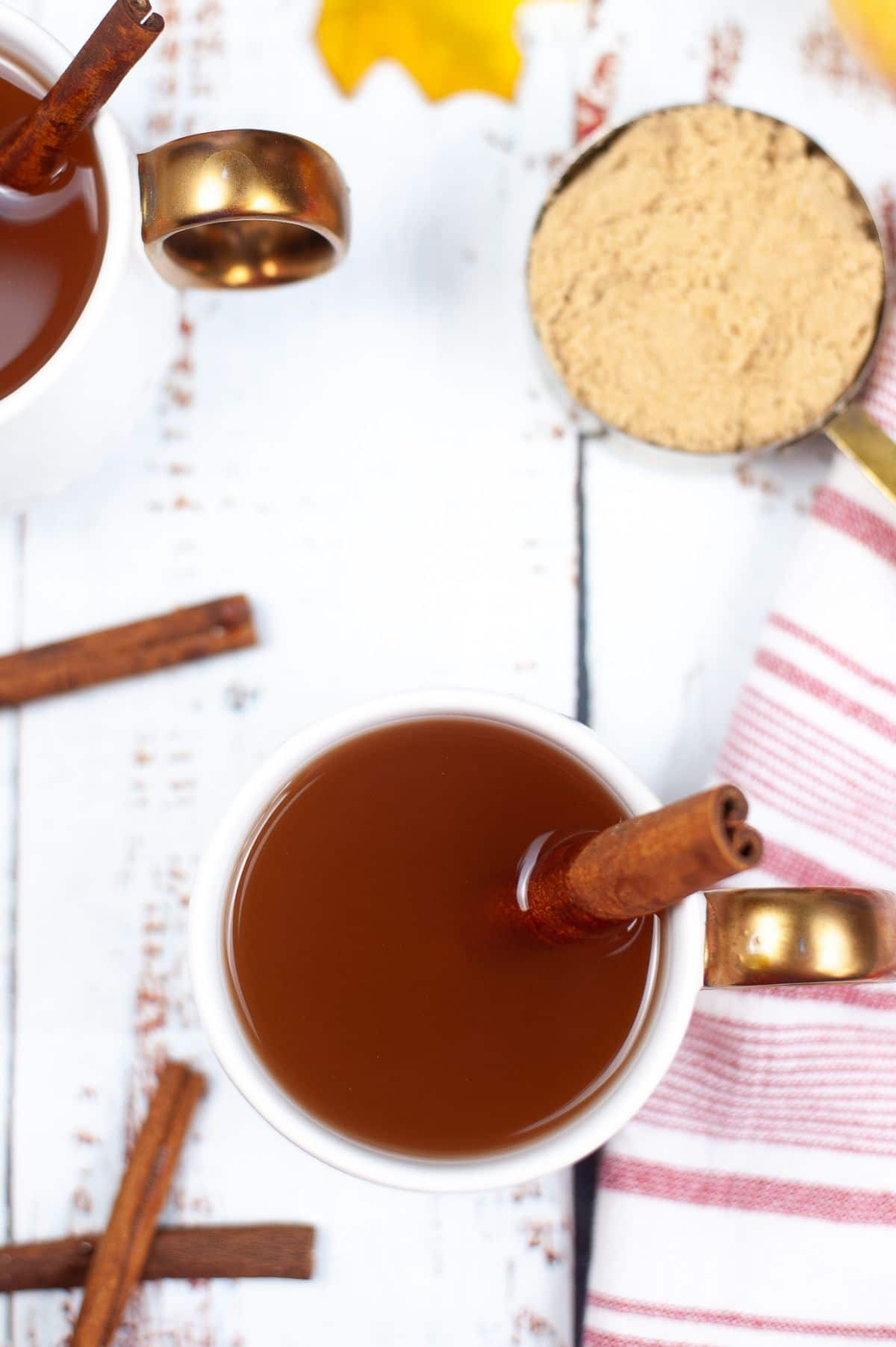 A vertical overhead shot of Instant Pot Apple Cider in a mug with cinnamon bark.