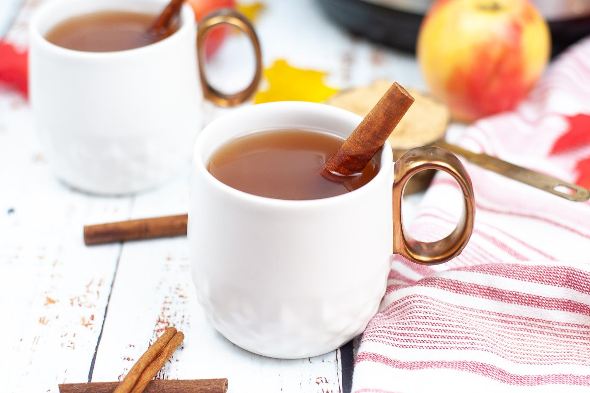 A horizontal image of two white mugs with Instant Pot Apple Cider and cinnamon bark, one mug centered, the other one on the left side blurred.