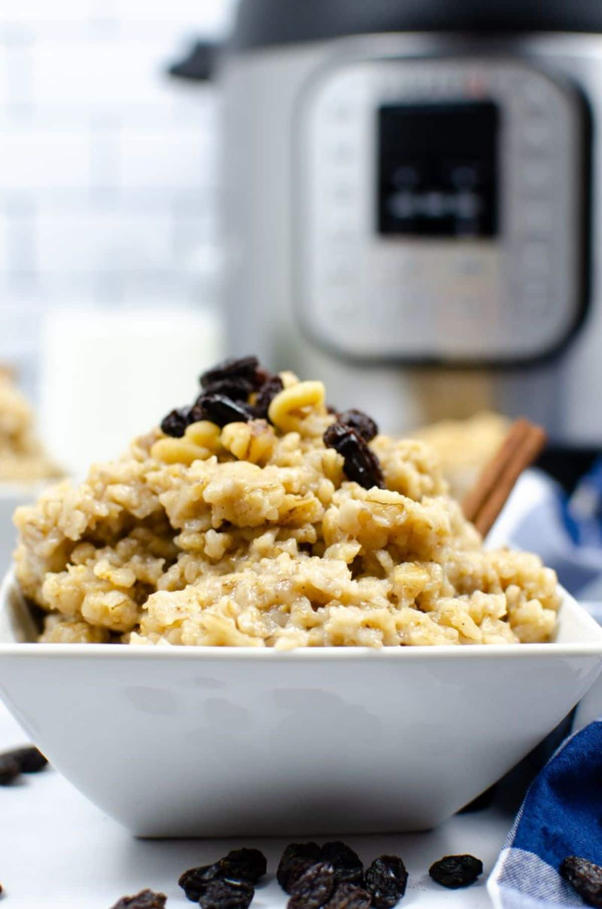 A vertical image of Instant Pot Oatmeal in a white square bowl topped with nuts and dried raisins and a blurred Instant Pot in the background.