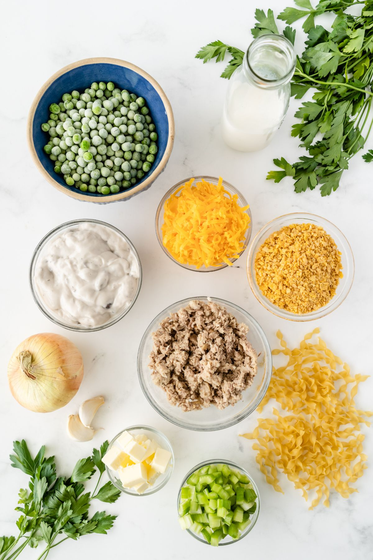 Ingredients needed to make a Tuna Noodle casserole in individual cups, saucers, and bowls.