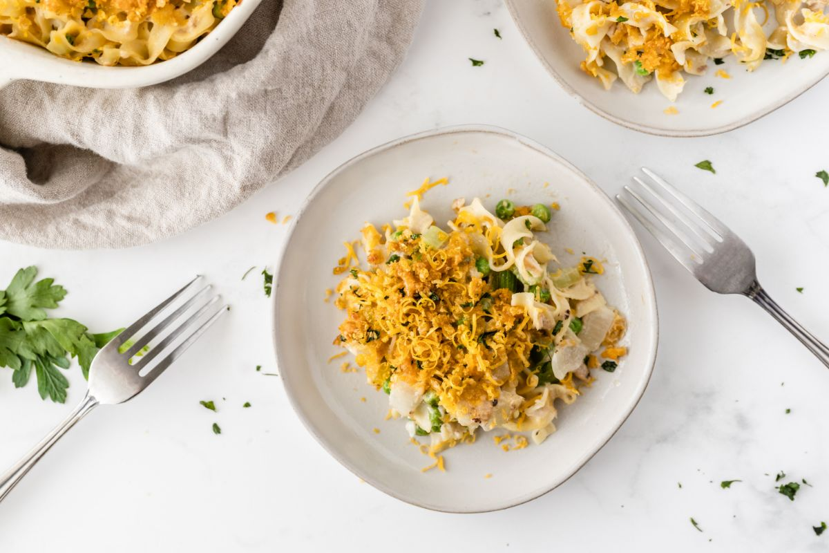 A horizontal overhead shot of tuna noodle casserole on a white plate with a fork on each side.