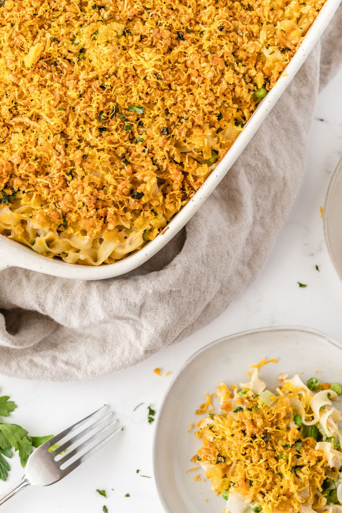 A vertical image showing a part of the tuna noodle casserole in the upper left corner and a small serving on a white plate in the lower right corner.
