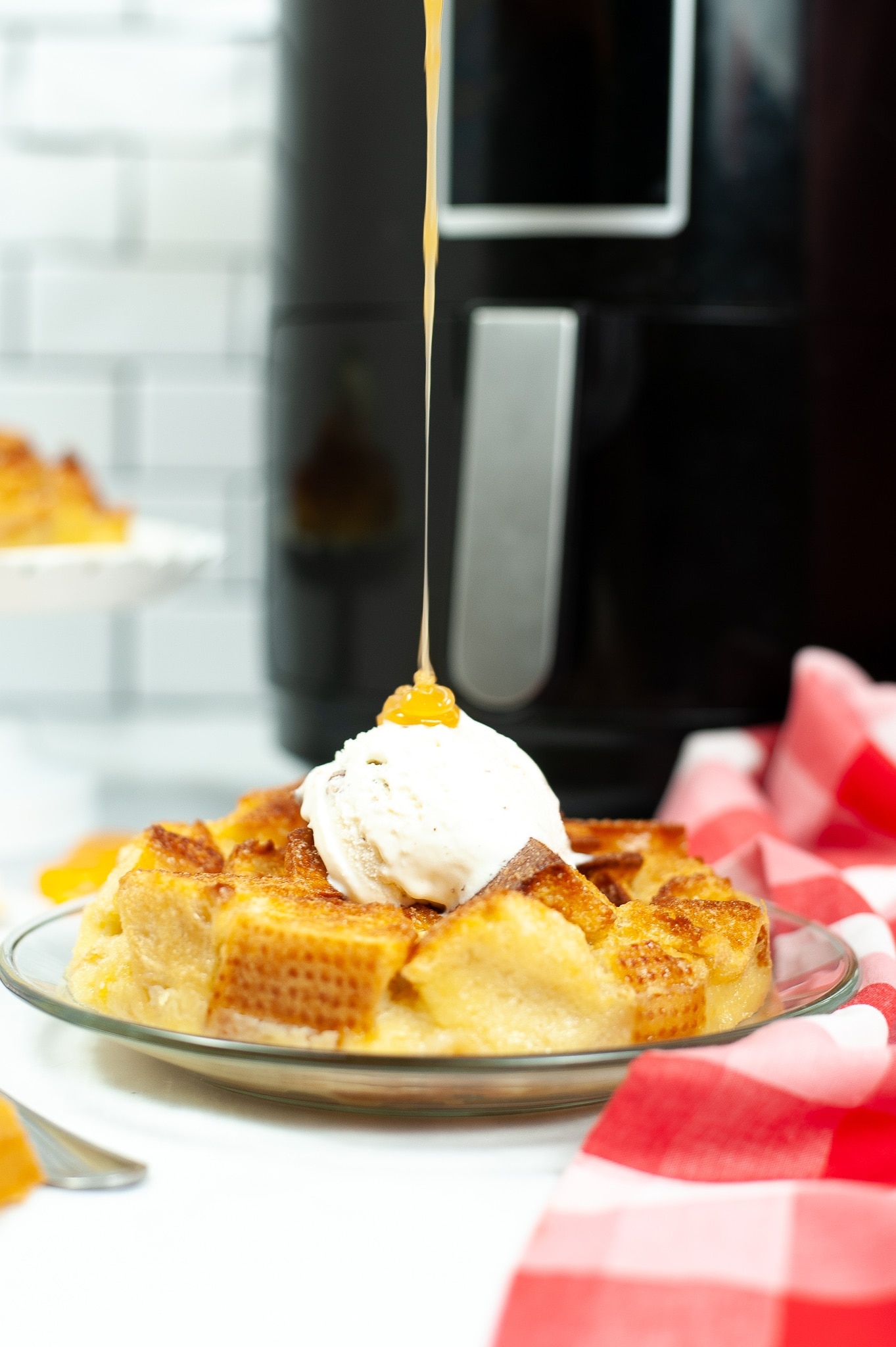 caramel sauce being poured on ice cream on top of air fryer bread pudding on plate